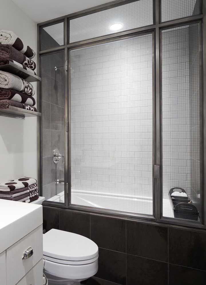 Ideia de banheiro pequeno com banheira e box; as portas de vidro seguram a água do banho