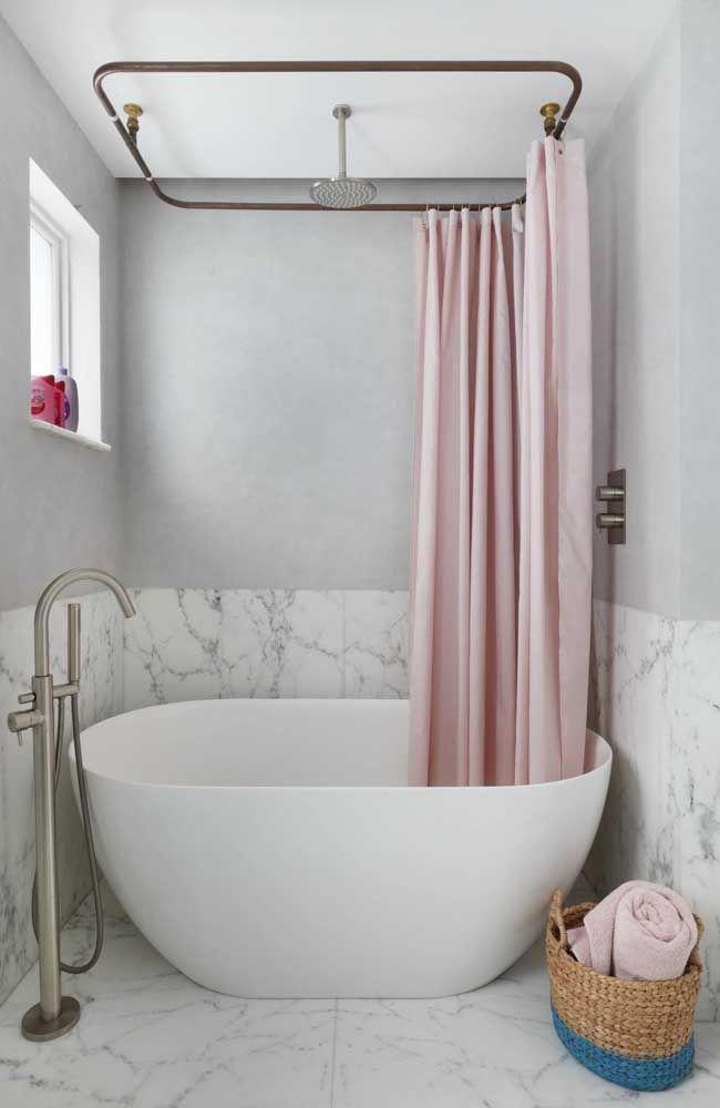 Banheira pequena oval, feita em cerâmica; destaque para a cortina cor de rosa que isola a área do banho
