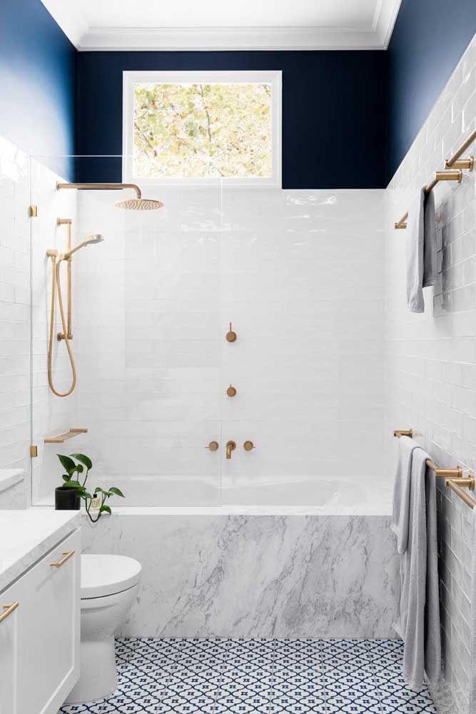 Banheira pequena de embutir, com porcelanato marmorizado e detalhes em dourado; uma linda opção para banheiro pequeno