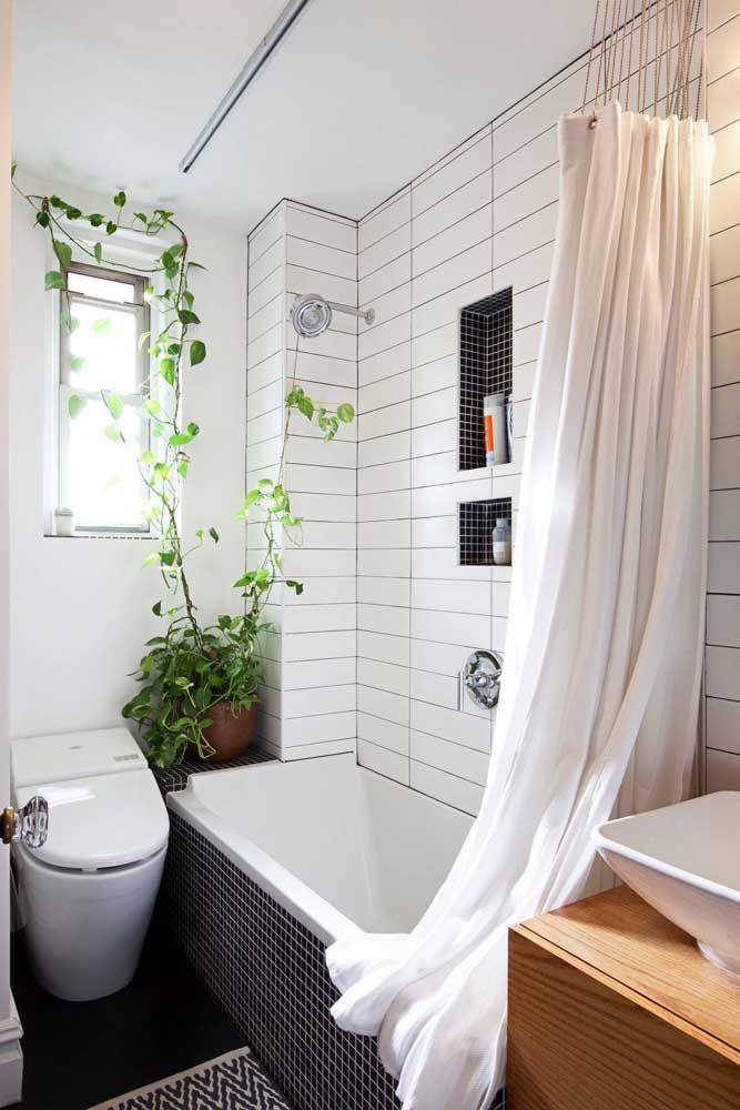 Banheira pequena em fibra, embutida em alvenaria; o espaço mínimo não foi impedimento para a instalação da banheira