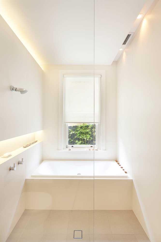 O banheiro super clean e pequeno ganhou como destaque a lindíssima banheira em cerâmica de embutir; esses modelos embutidos podem contar com hidromassagem