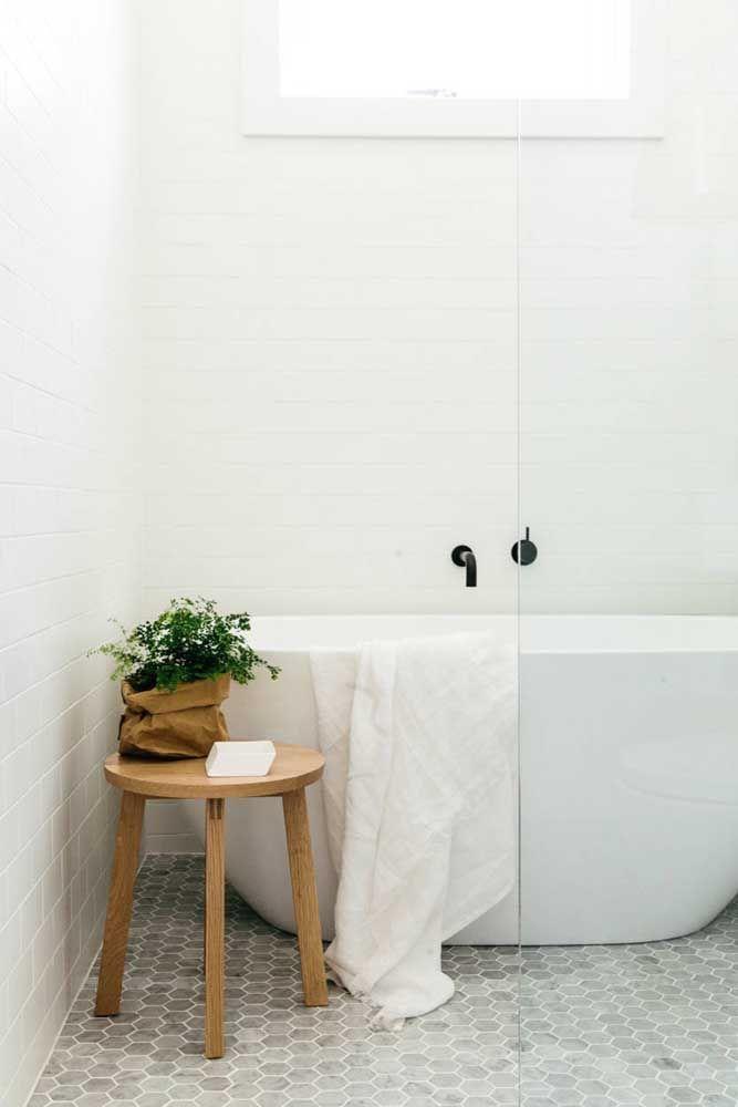 O banheiro branco e clean traz uma banheira branca destacada pela torneira preta