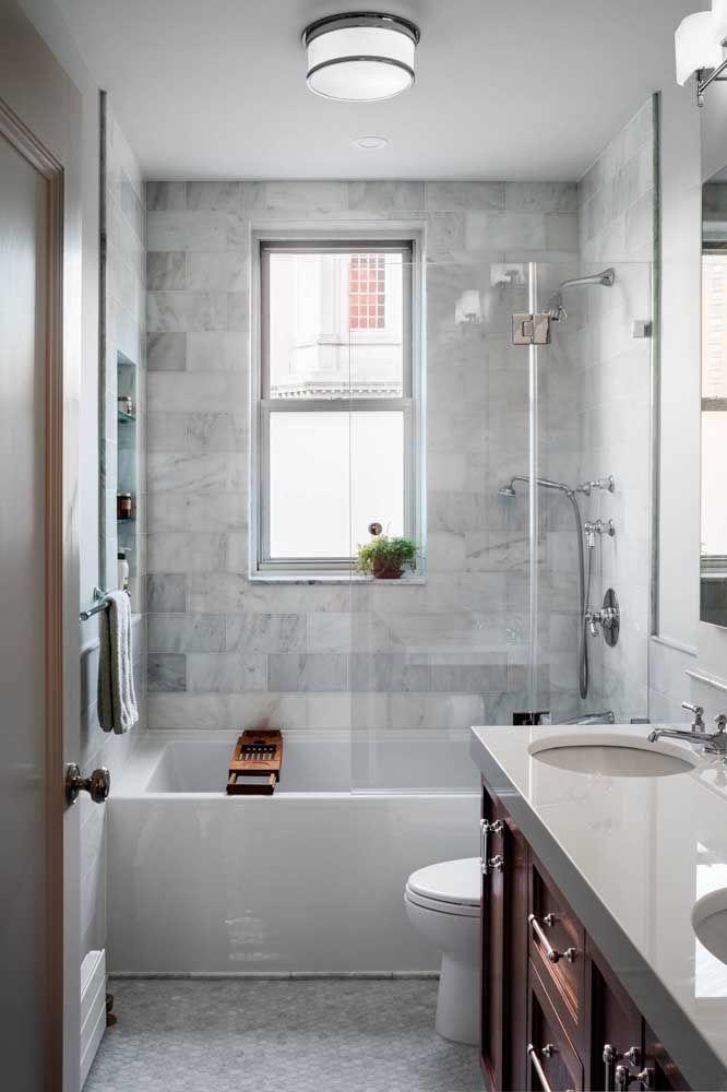 Banheira simples e chuveiro compartilhando o mesmo espaço no banheiro pequeno