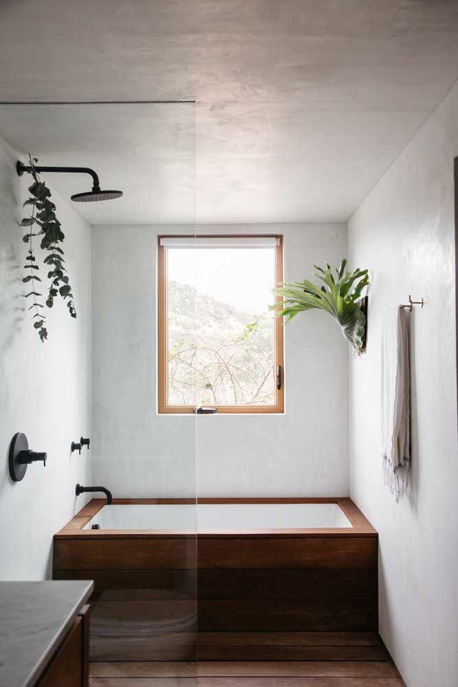 Banheira pequena aproveitando todo o espaço de largura do banheiro pequeno; o acabamento em madeira dá um toque todo charmoso à peça