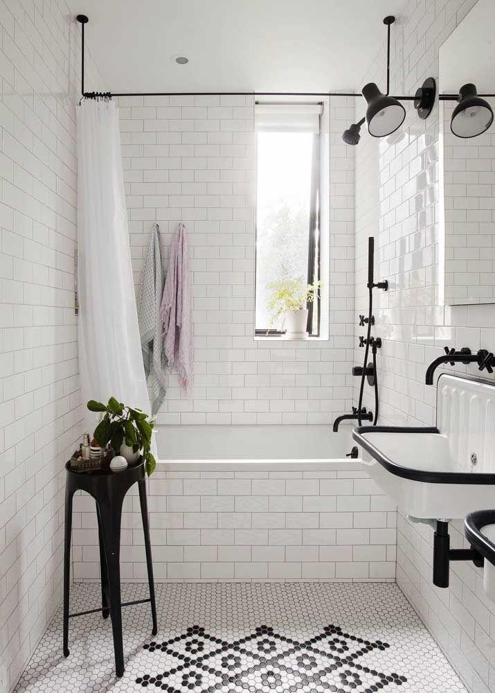 Os metais pretos destacam a banheira pequena e simples de alvenaria
