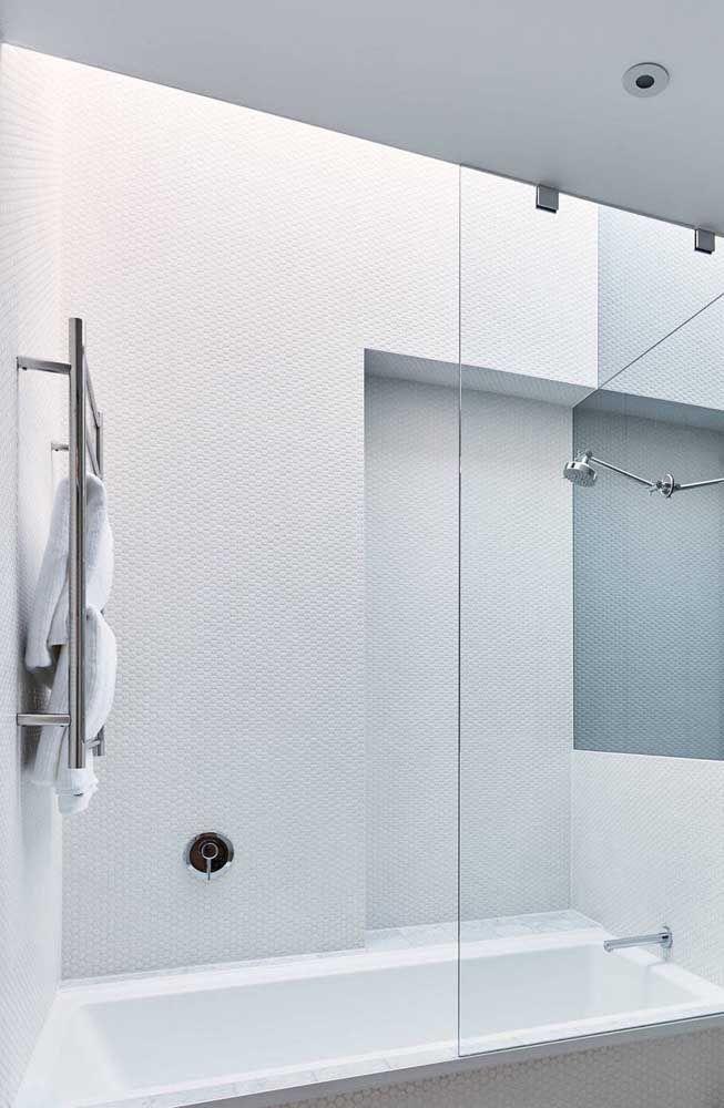 Banheira de embutir em cerâmica para banheiro pequeno com box; a iluminação diferenciada sobre a banheira deixa o momento do banho ainda mais agradável
