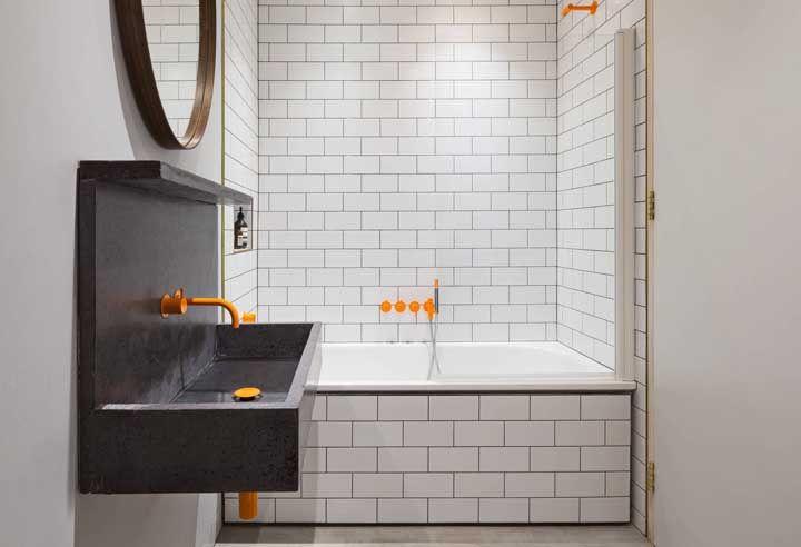 O banheiro pequeno driblou a neutralidade da banheira simples com metais de cor laranja