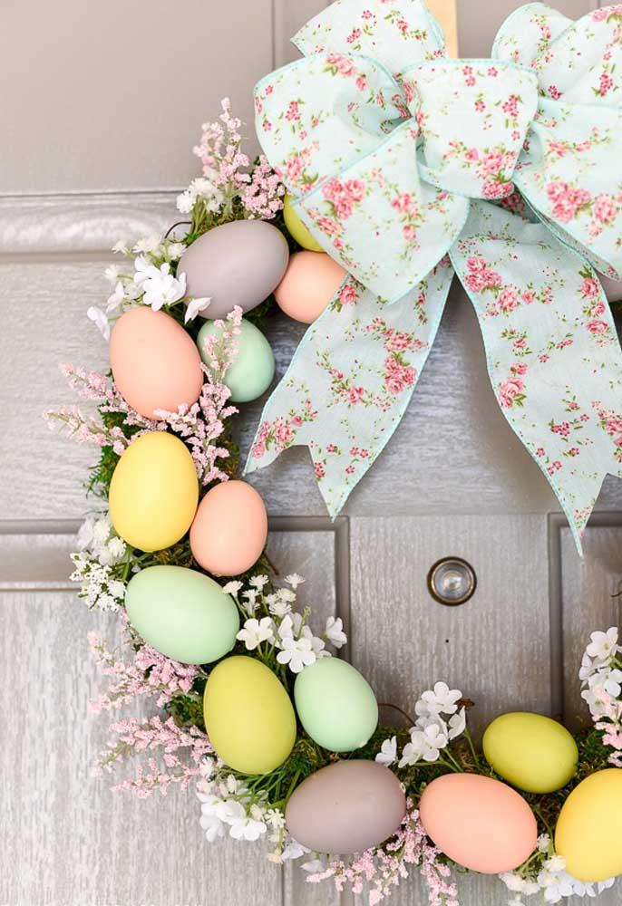 Não tem ideia de enfeites de páscoa? Olha essa guirlanda feita com ovos coloridos e flores.