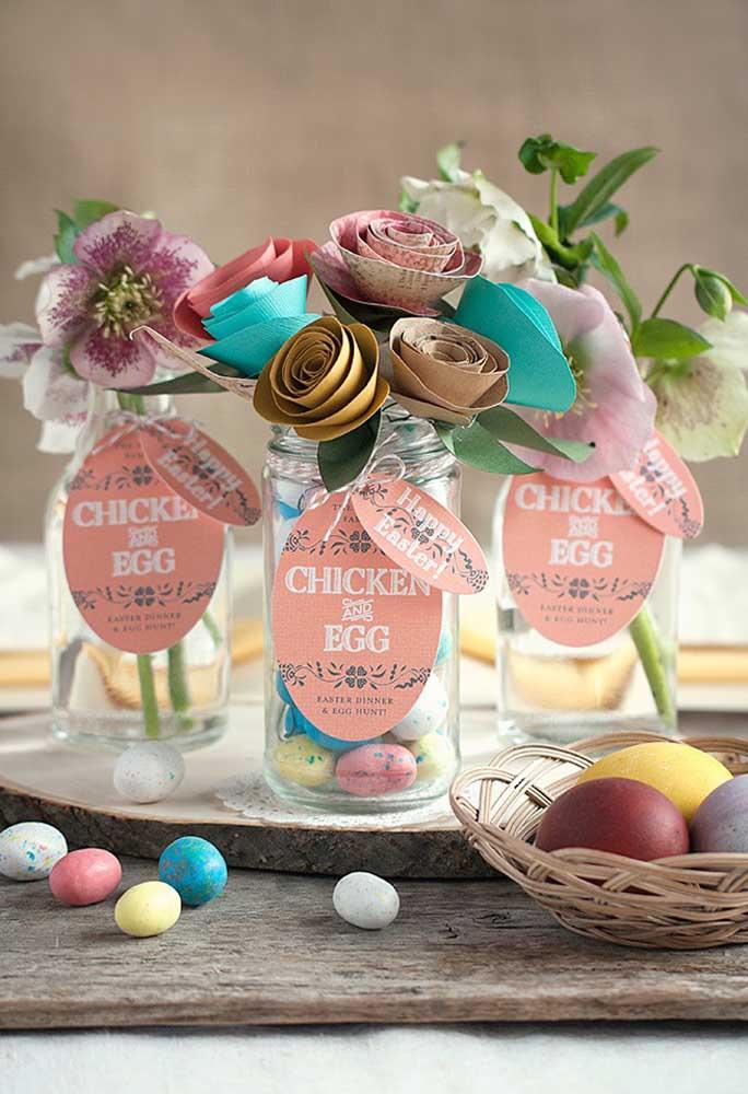 O que acha de você mesmo colocar a mão na massa para fazer o enfeite de páscoa? Para isso, pegue potes de vidros que não usa mais, faça um arranjo de flores com papel e encha o pote com ovinhos coloridos.