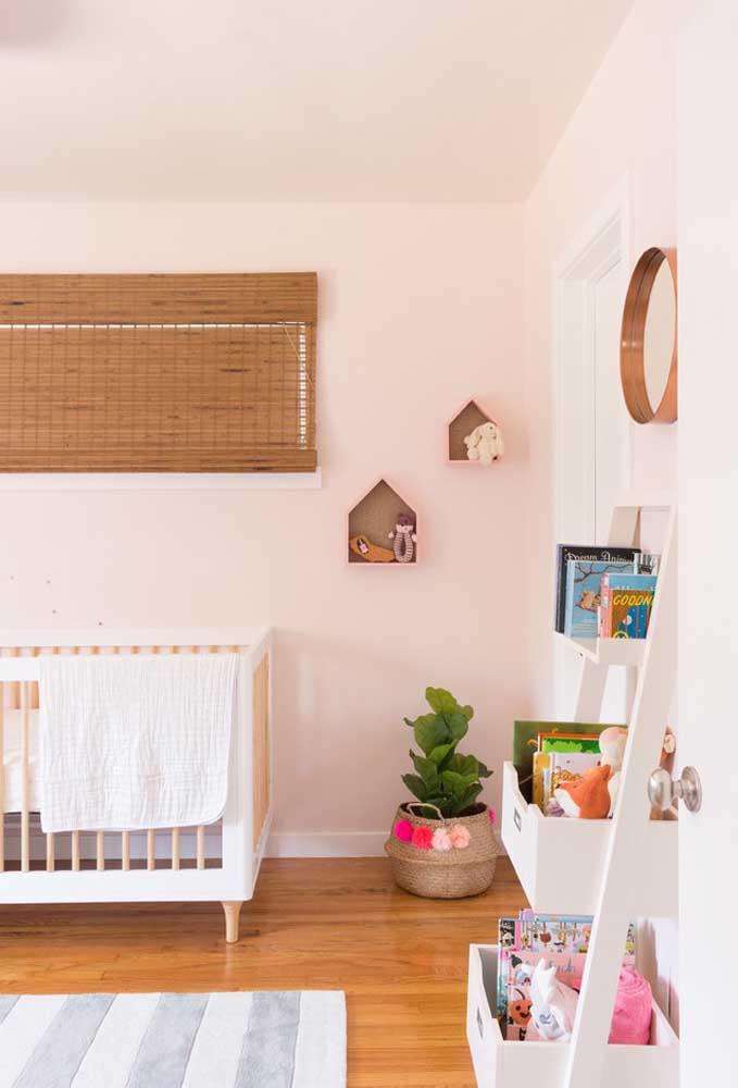 A combinação entre piso de madeira e parede na cor rosa deixou o quarto do bebê mais aconchegante.