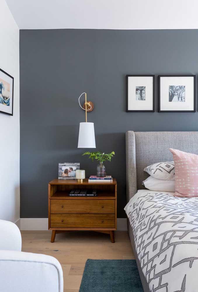 Para destacar a parede do quarto, pinte de cinza escuro e aposte em móveis mais claros.