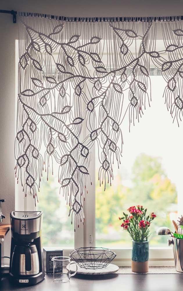 Com desenhos de folhas, essa pequena cortina de crochê é o destaque da cozinha; repare que ela foi pendurada por um galho de árvore
