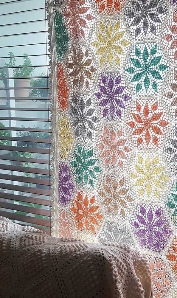 A janela com persiana investiu em uma cortina de crochê para finalizar a decoração
