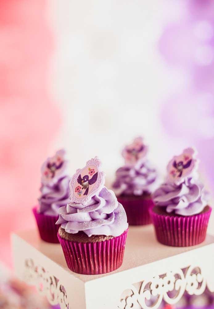 Use pasta americana na cor do tema para decorar o topo do cupcake e use um belo enfeite que faz referência ao tema Princesa Sofia.