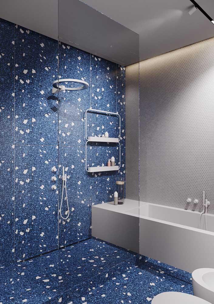 Nesse banheiro de luxo a área do banho ganhou portas de vidro e um revestimento azul que se estende até o piso