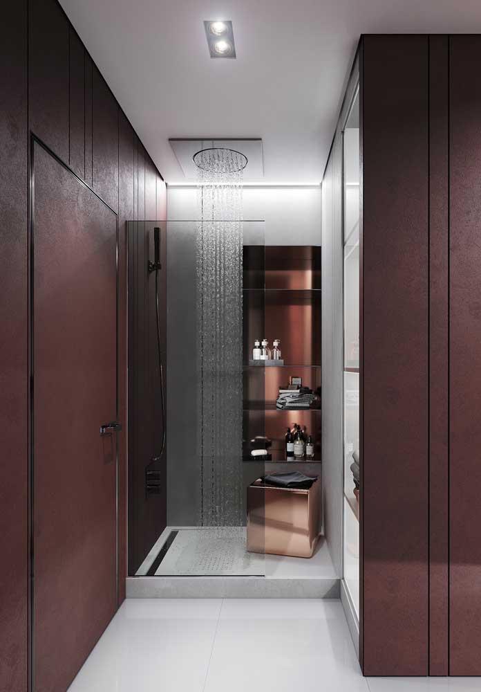 Já esse outro banheiro de luxo traz paredes terrosas e um chuveiro instalado diretamente no teto
