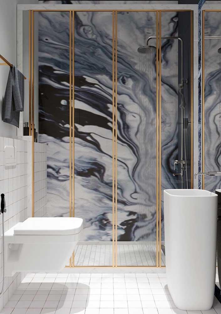 O efeito marmorizado e a moldura dourada são os grandes destaques desse banheiro luxuoso