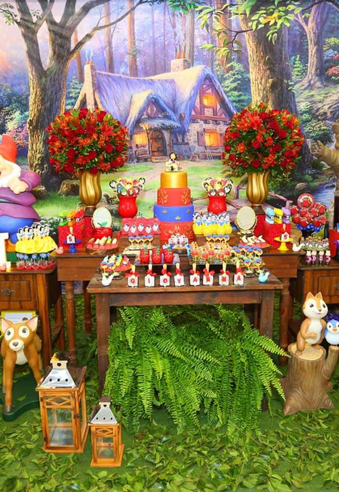 Decoração da mesa do bolo da festa Branca de Neve. As cores da personagem são o grande destaque
