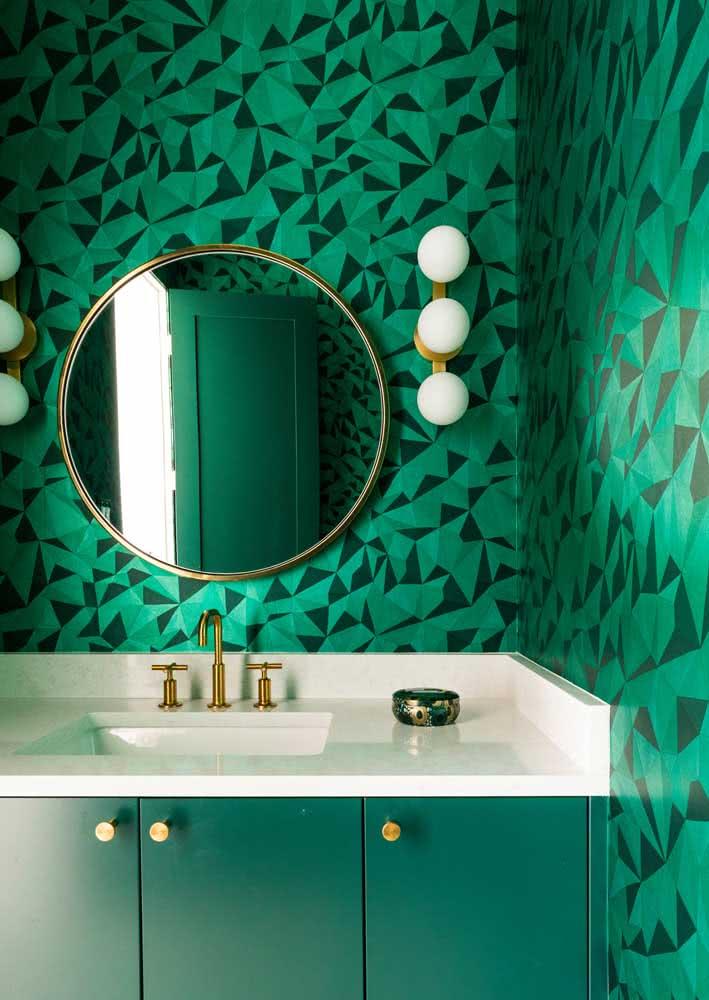 Em um banheiro verde, o papel de parede escolhido acompanha a cor por toda a parede em desenhos geométricos.