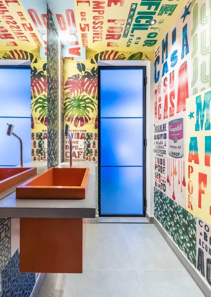 Banheiro com papel de parede com estilo urbano e latino instalado nas paredes laterais e no teto do espaço.