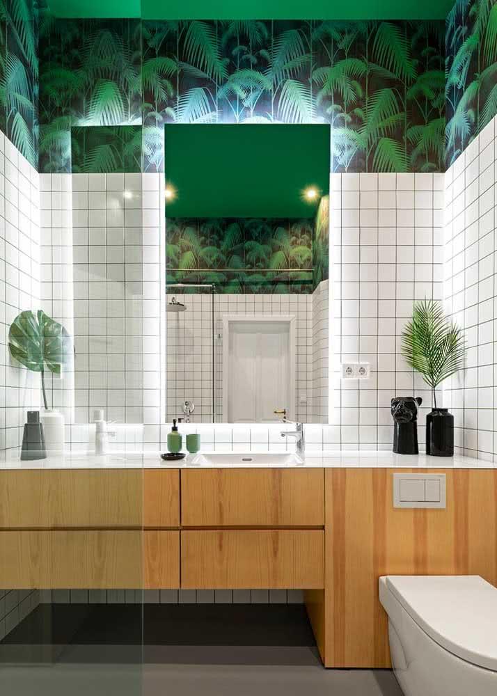 Traga a floresta para dentro do seu banheiro com um incrível papel de parede. Neste exemplo, a parte superior das paredes foi revestida com o papel ao invés do tradicional azulejo.