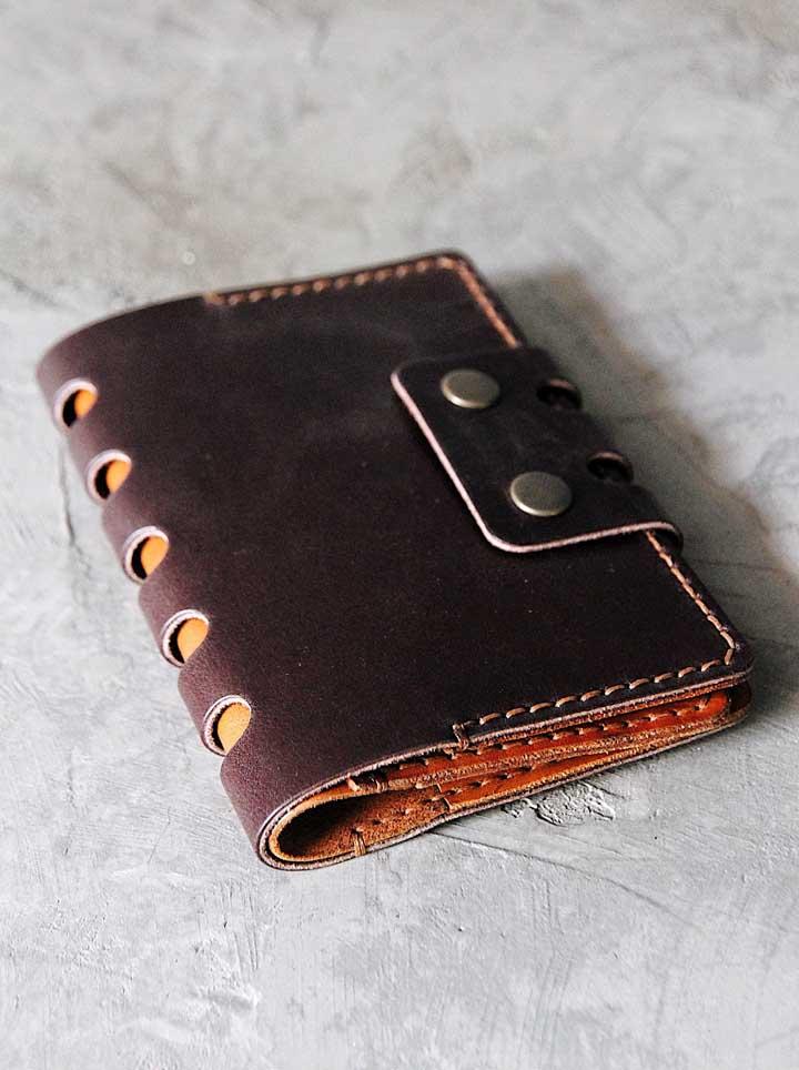 Porta passaporte de couro com botões e detalhes em tom de couro mais claro; charme e elegância para o documento
