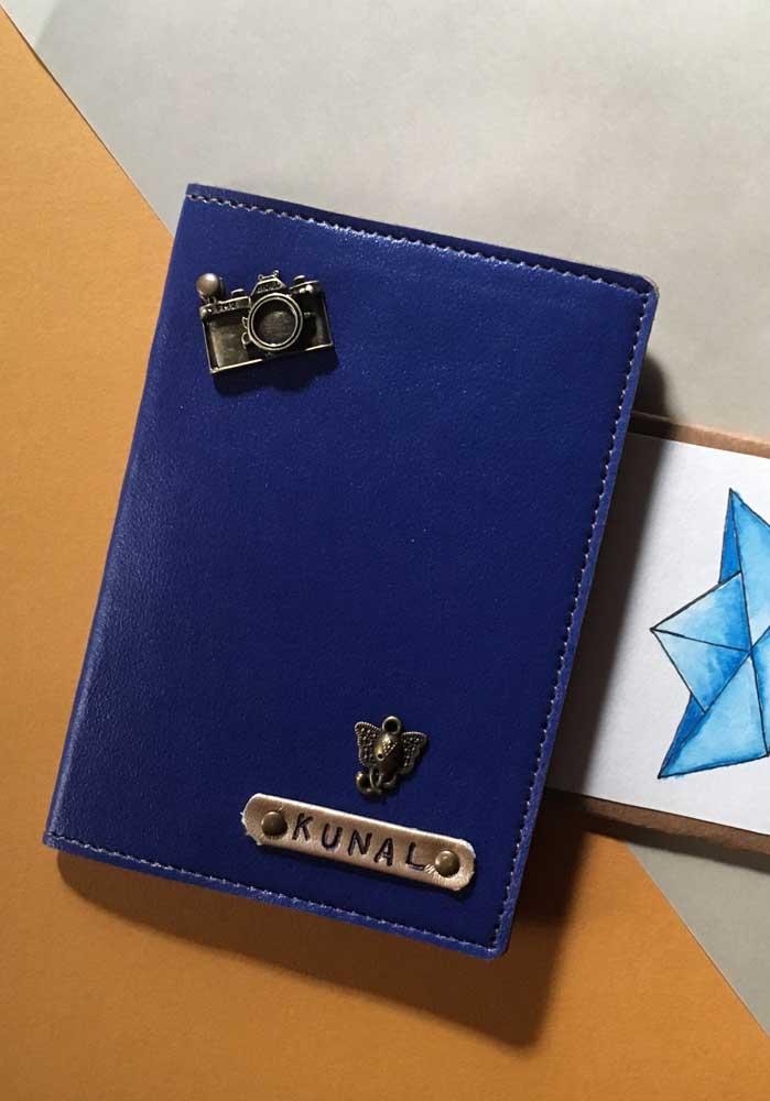 Porta passaporte em couro com aplicações de pingentes de metal e nome impresso na placa