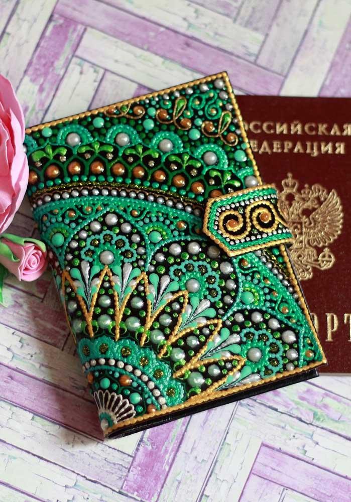 Porta passaporte com colagens em pedras e contas; o formato em mandala é o grande destaque da peça