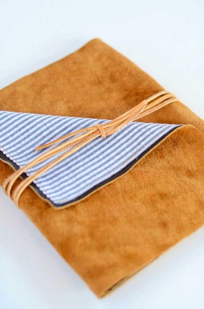 Porta passaporte em tecido, com detalhes em camurça e fita em corino para amarrar o item; uma ideia rústica e super prática para guardar seus documentos