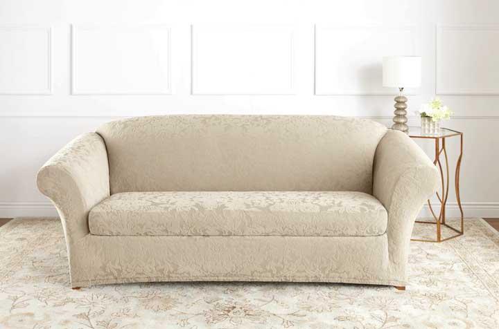 O jacquard em tom claro e neutro combinou perfeitamente com o design elegante e sofisticado do sofá; repare que o tapete possui uma semelhança de cor e estampa muito próxima do tecido