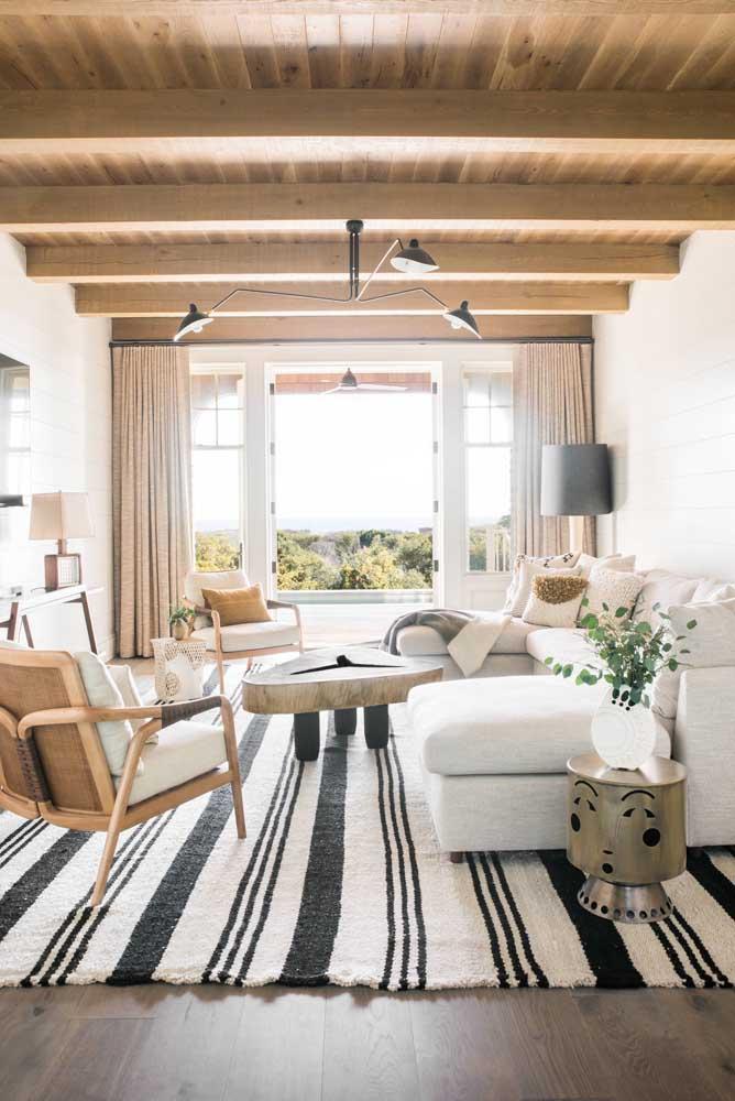 O cúmulo da elegância é um sofá de linho branco; nem o toque rústico da sala consegue disfarçar a sofisticação do estofado