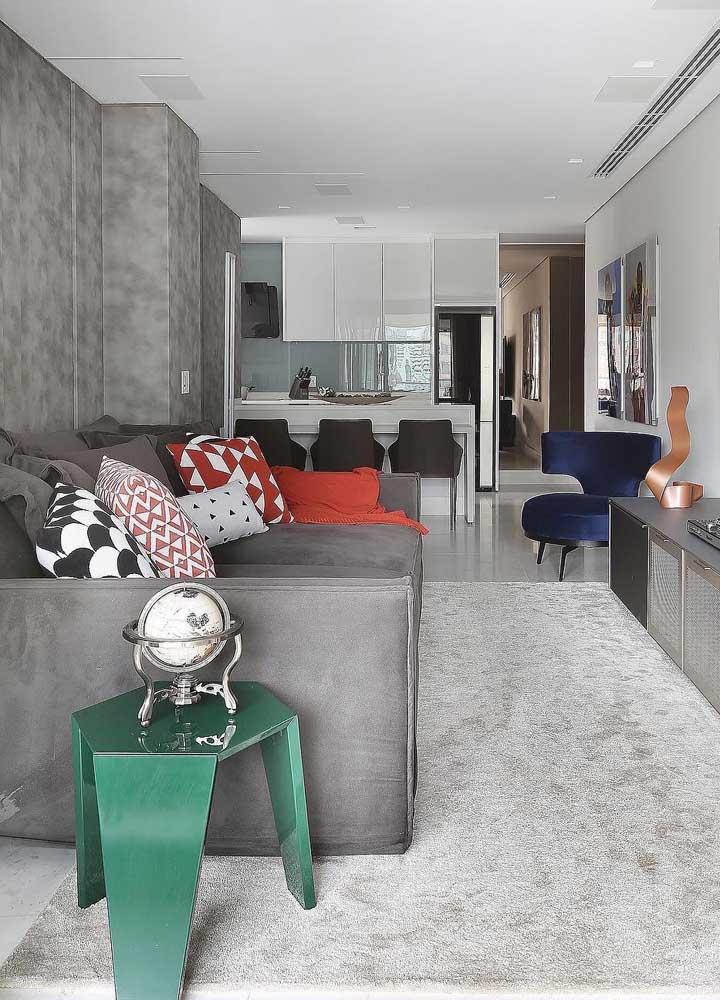 O cinza mais escuro do sofá em suede se encaixou perfeitamente nessa decor jovial