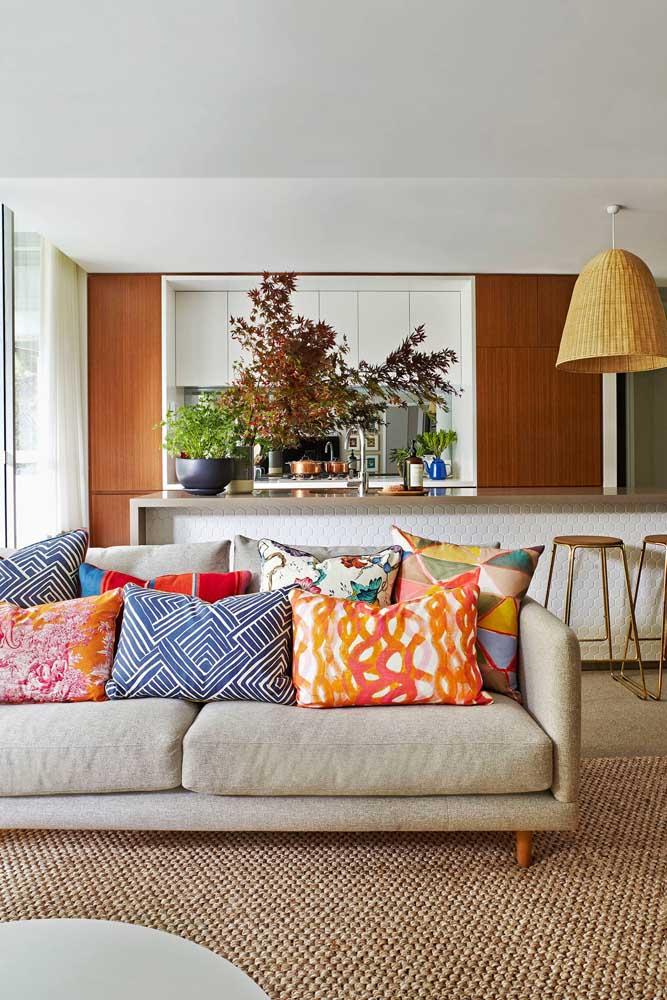 O sofá de chenile bege ficou ainda mais confortável com as inúmeras almofadas coloridas sobre ele