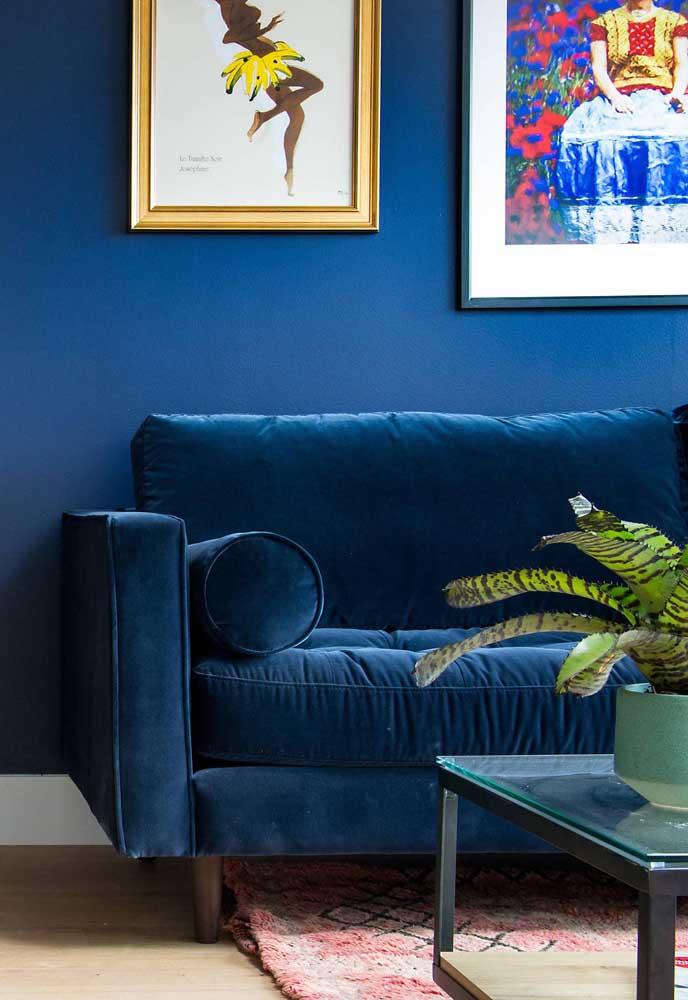 Sofá de veludo azul e parede no mesmo tom se fundem nessa sala em um verdadeiro mimetismo decorativo