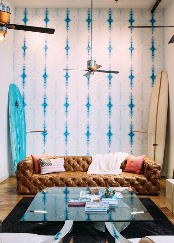 Sofá de couro sintético com acabamento em capitonê: um modelo clássico para contrastar com a decoração moderna e despojada da sala