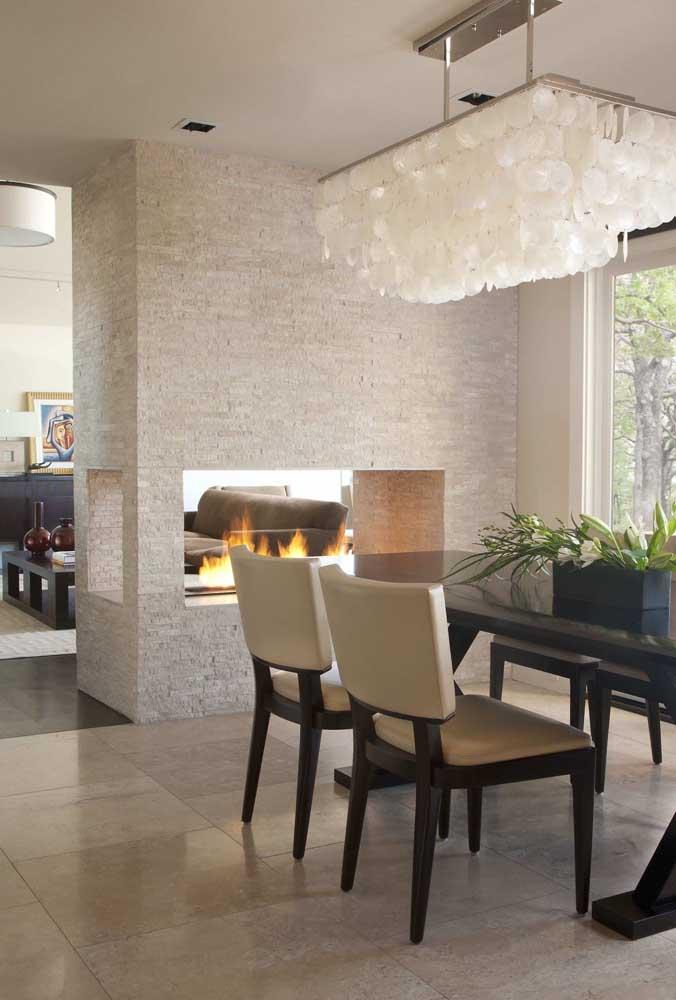 Que design belíssimo desse ambiente! A lareira tem saída para dois ambientes da casa e contou com a canjiquinha para completar a composição