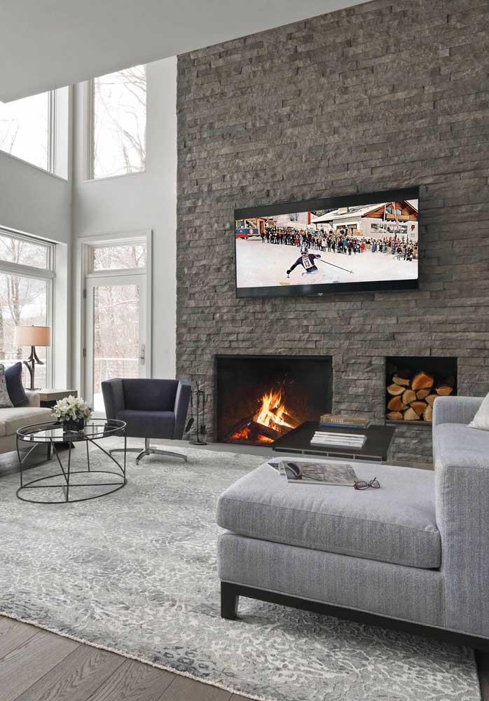 Aqui, TV e lareira dividem o espaço da parede em canjiquinha cinza