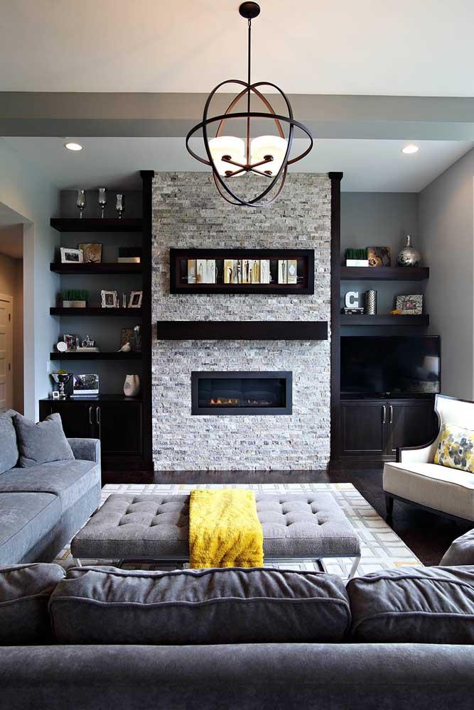 Parede da lareira em canjiquinha cinza claro; os móveis pretos formam uma moldura interessante ao redor das pedras