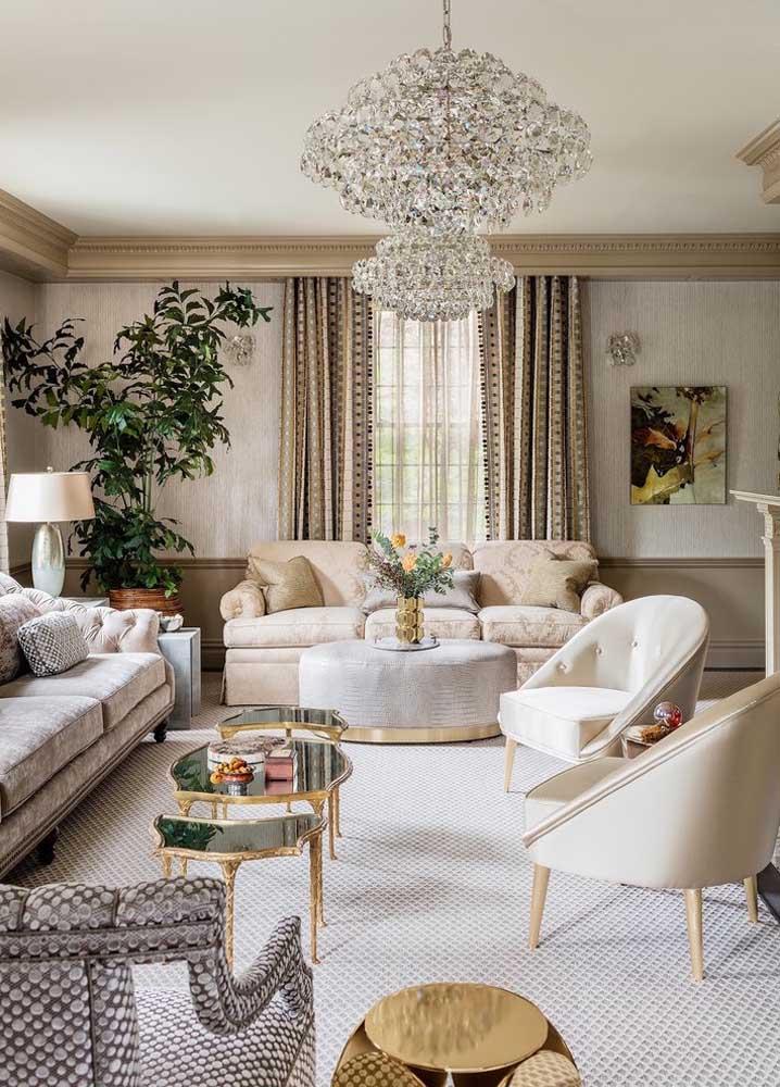 A sala clássica e elegante apostou em um tapete grande cinza levemente estampado para demarcar toda a área