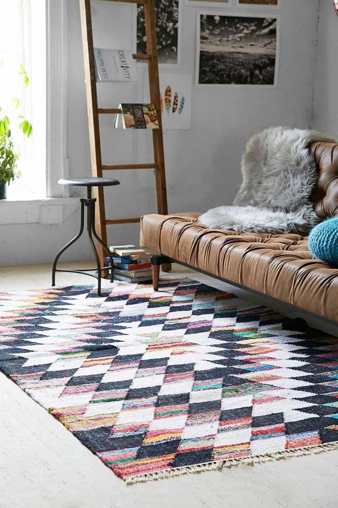 A sala estilosa e cheia de personalidade traz um tapete de cores variadas e estampas geométricas