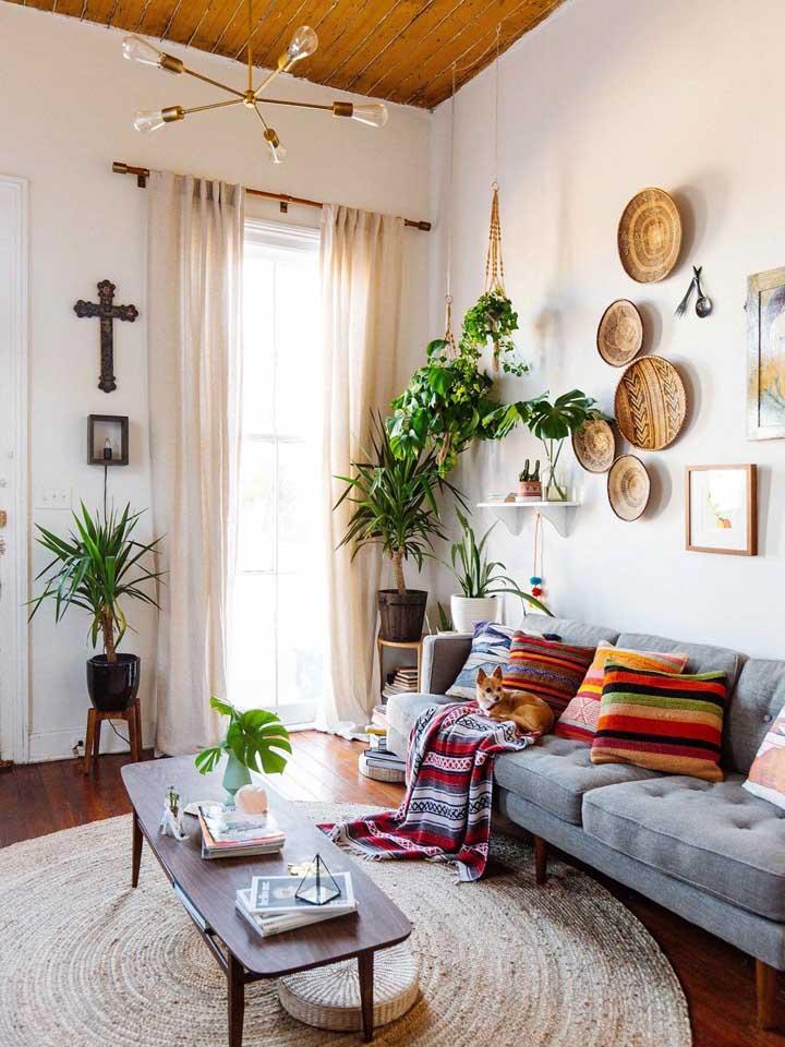 Aqui nessa sala, a irreverente decoração boho contou com a beleza moderna do tapete redondo cobrindo todo o centro do ambiente