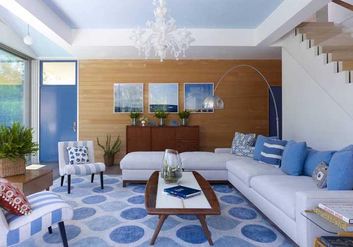Os tons de azul dominam a decoração dessa sala, sendo usados sem medo do tapete até a cor da porta
