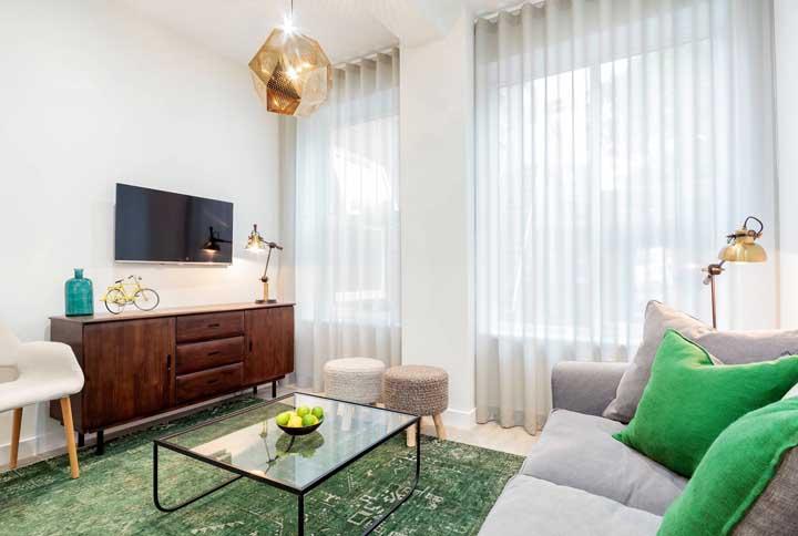 Não muito comum, o tapete verde se destaca na decoração dessa sala pequena e combina muito bem com o rack de estilo retrô