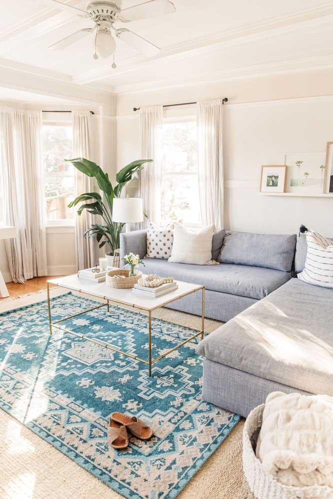 O azul claro suave e a estampa discreta do tapete formam uma combinação equilibrada e elegante para a sala
