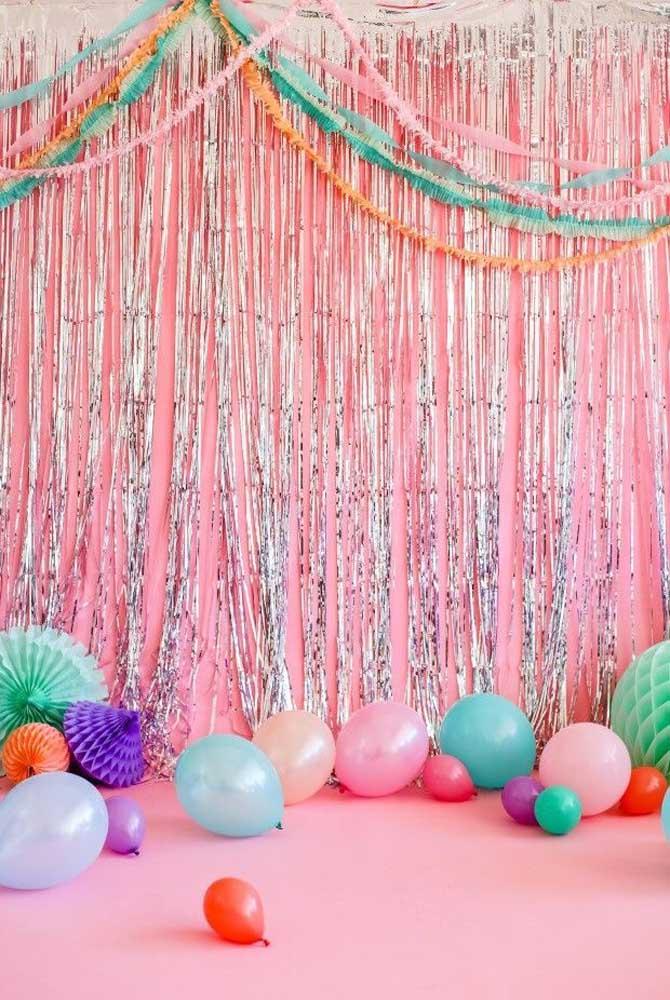 Painel feito com tiras brilhantes, balões e enfeites de papel