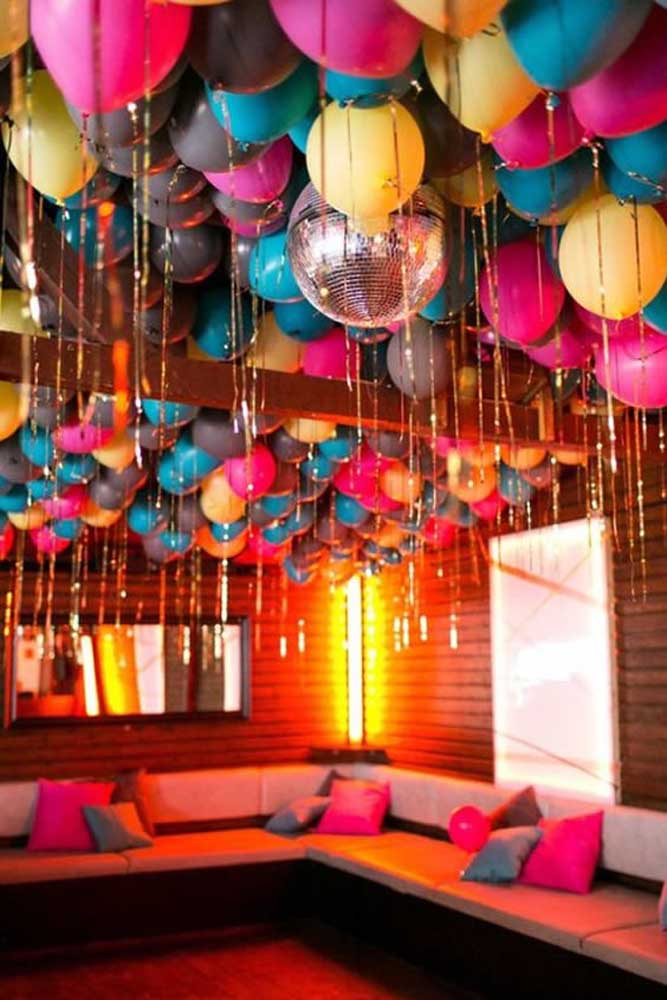 Luzes, balões e tiras brilhantes formam esse cenário de festa anos 80