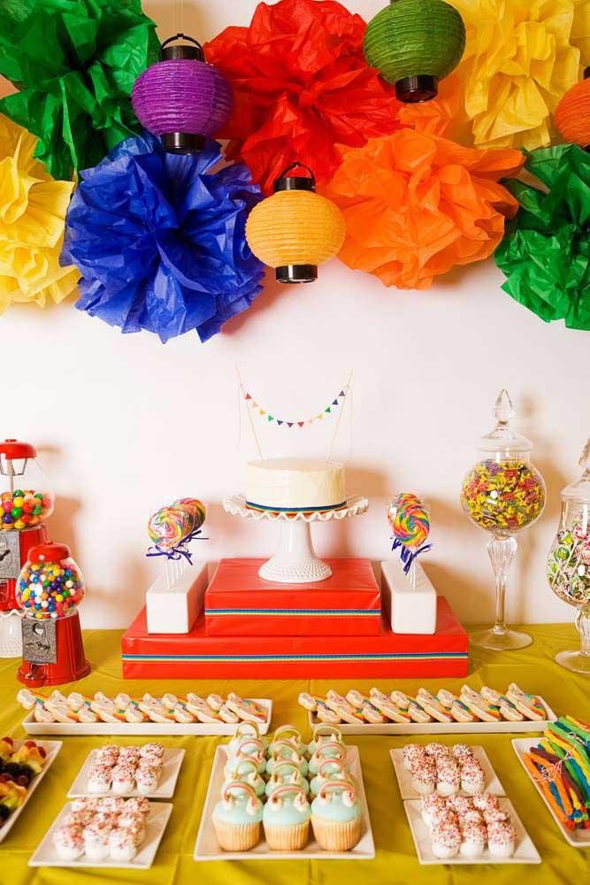 As flores de papel criam o painel de fundo para a mesa de bolo dessa festa anos 80