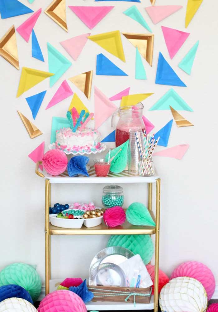 A decoração dessa festa anos 80 foi feita com recortes de pratos de papel coloridos colados na parede