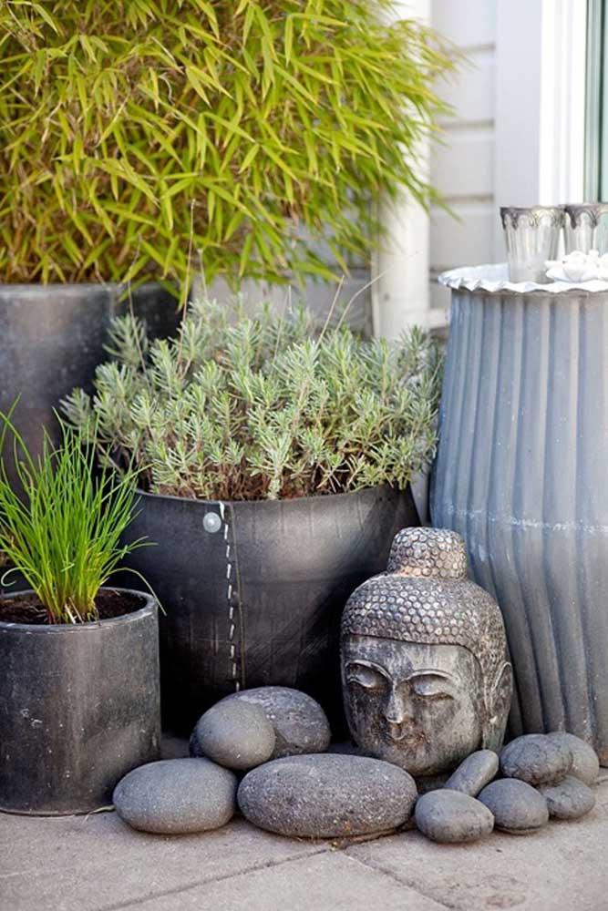 Mini área verde na entrada de casa montado com vasos, pedras e estátua