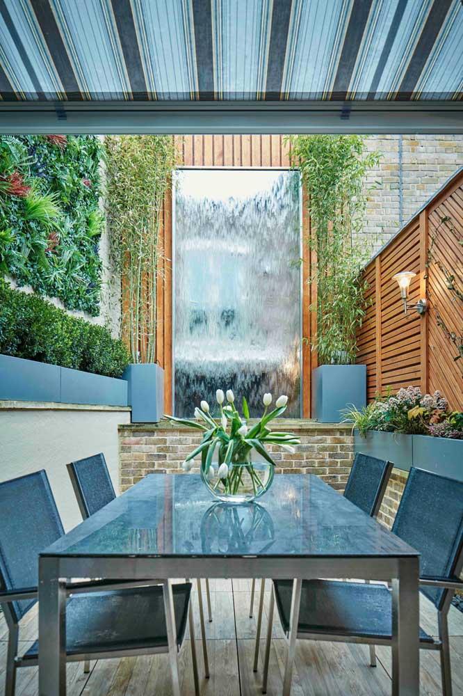 A sala de jantar integrada a área externa ganhou um jardim vertical e pequenas árvores de bambu